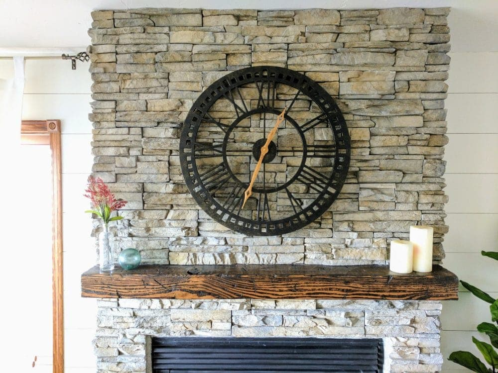 distressed wood beam mantel on stacked stone fireplace with clock above