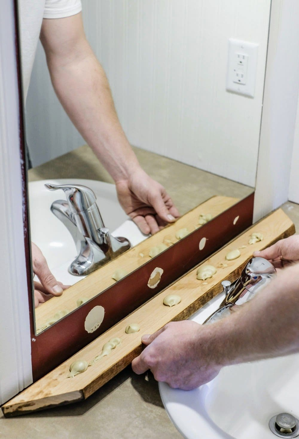 installing wood trim around a bathroom mirror