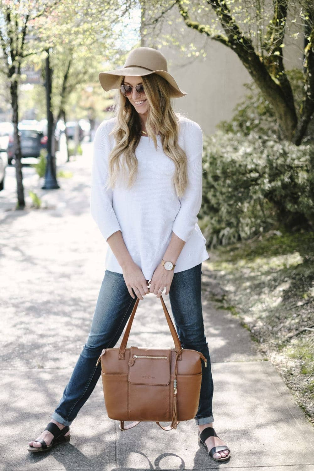 diaper bag review featuring a blonde woman holding leather bag on sidewalk
