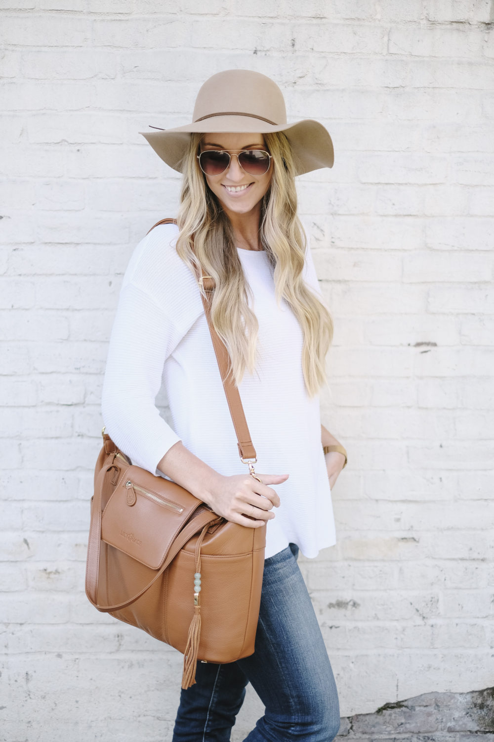 blonde woman carrying leather diaper bag with messenger strap on shoulder