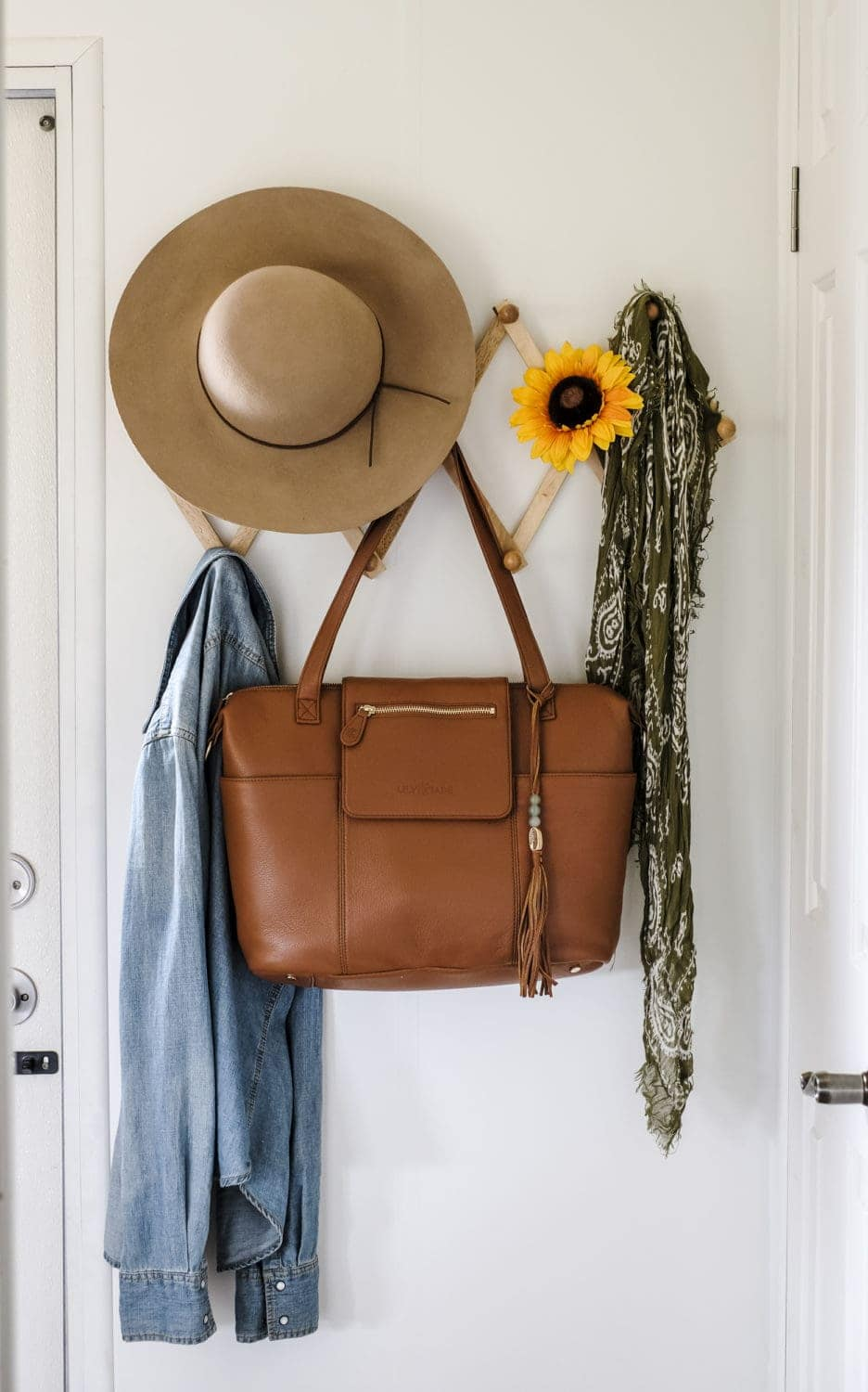 leather diaper bag hanging on coat rack