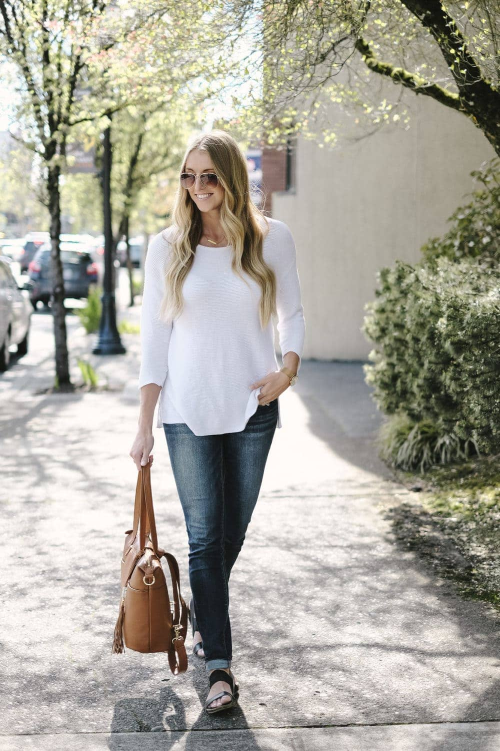 blonde woman holding lily jade diaper bag in camel leather