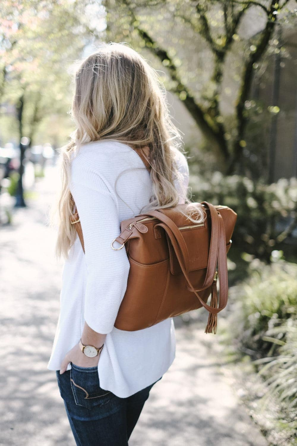 blonde woman with leather diaper bag backpack