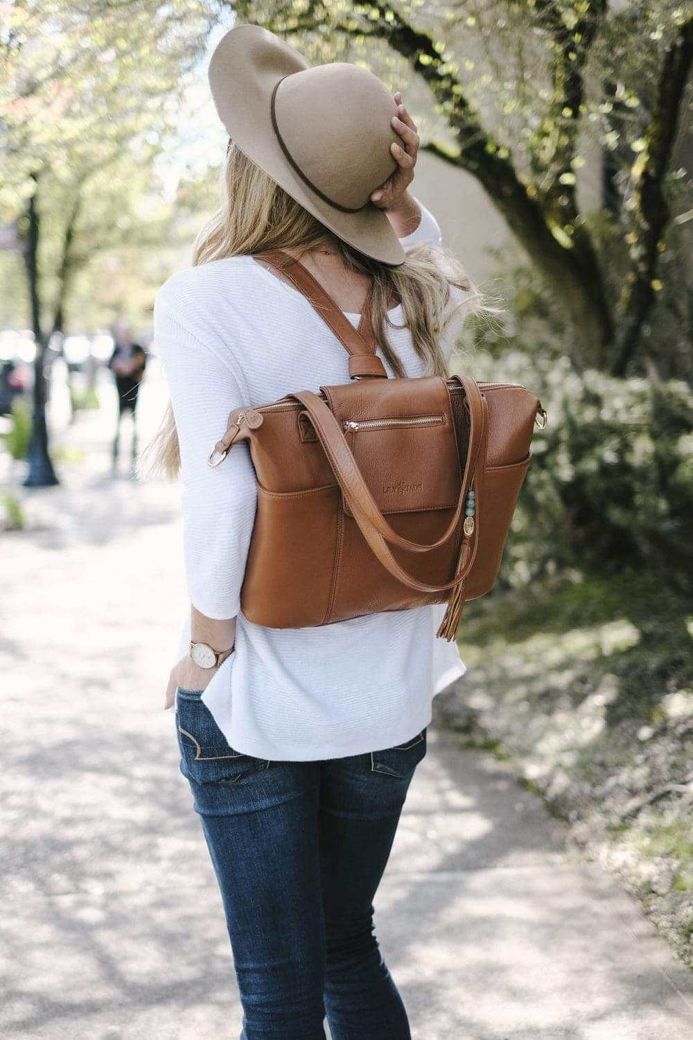 lily jade diaper bag in camel leather worn as a backpack
