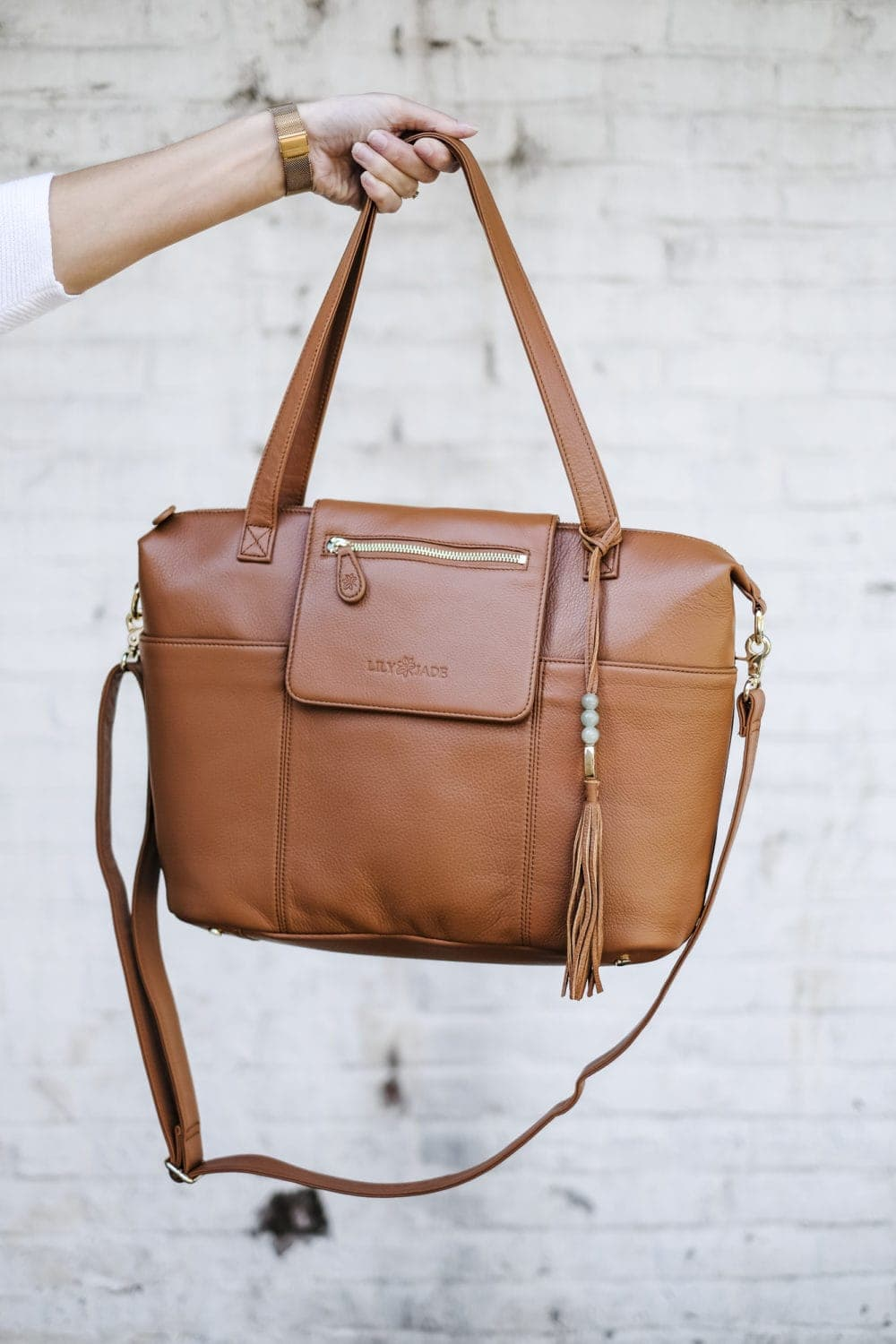 leather diaper bag with multiple straps held in front of white wall