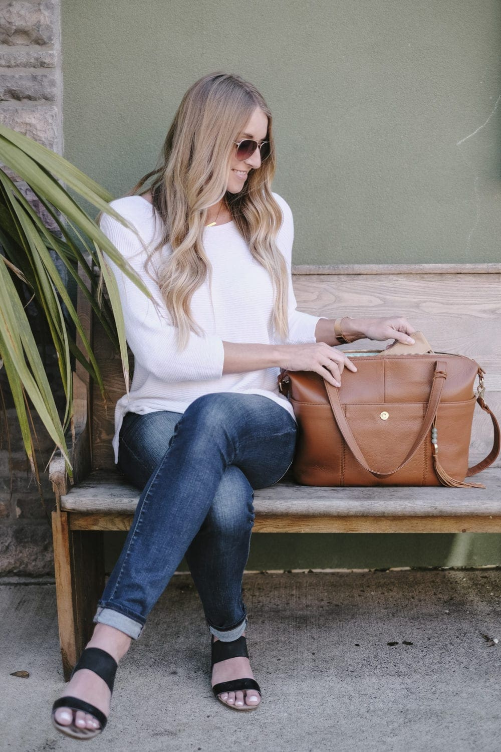 Blonde woman sitting next to lily jade diaper bag on a bench
