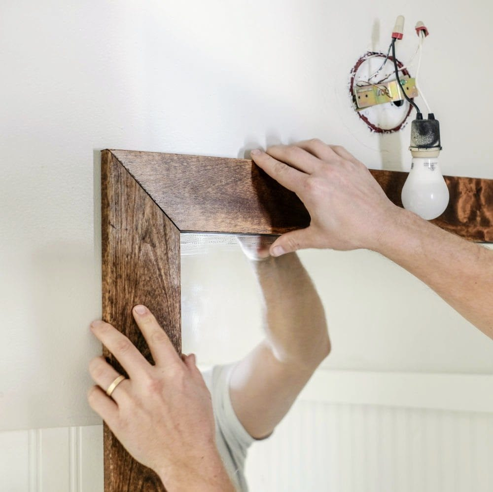 installing wood boards onto the wall around a bathroom mirror