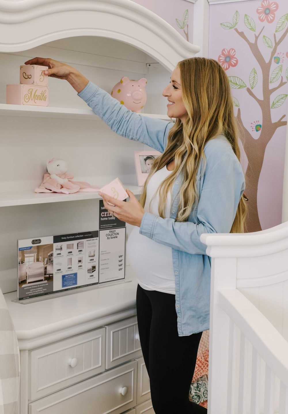 pregnant woman arranging blocks in a nursery set in store