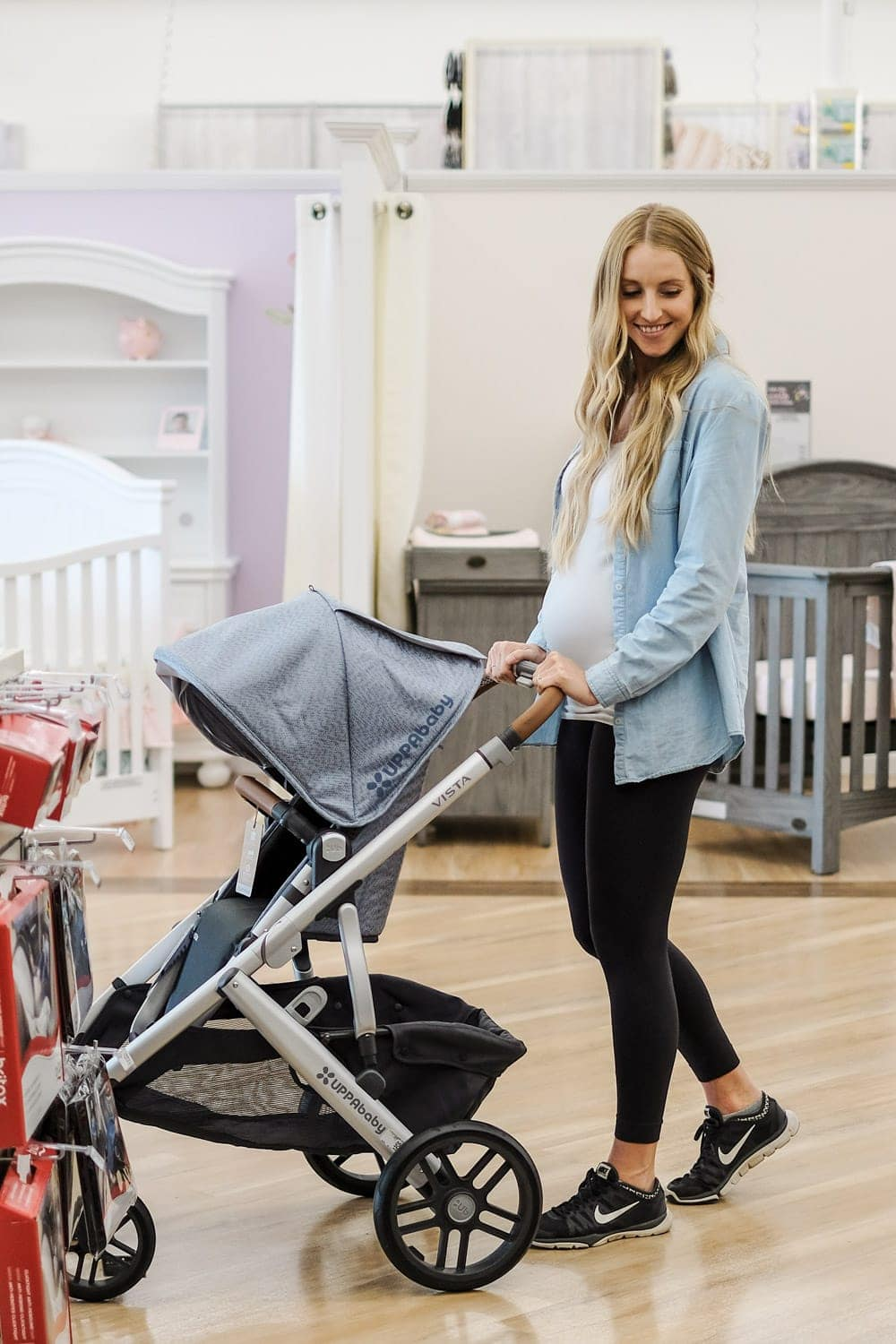 blonde woman pushing stroller in store