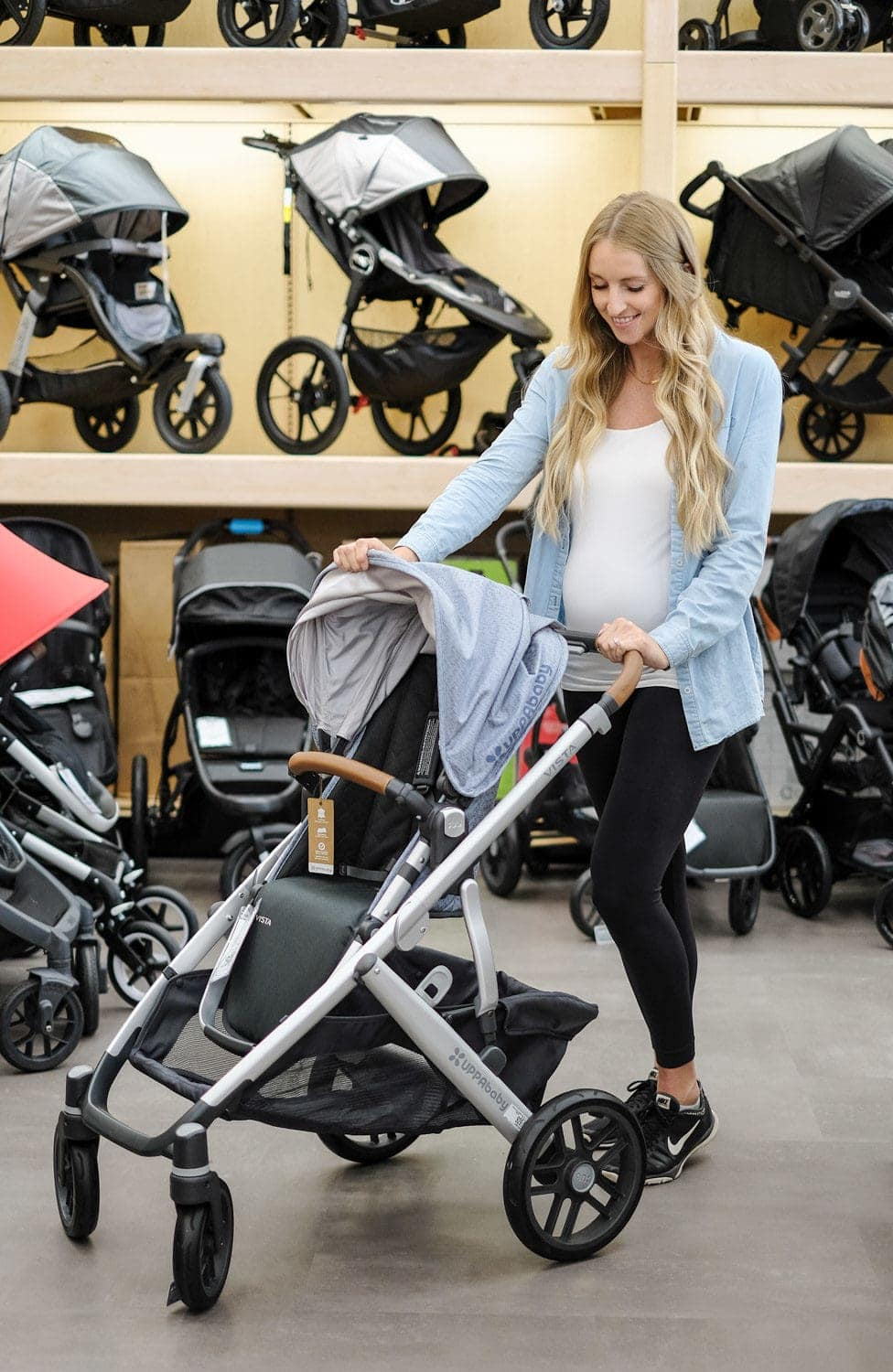 blonde woman testing out stroller in store at buy buy baby