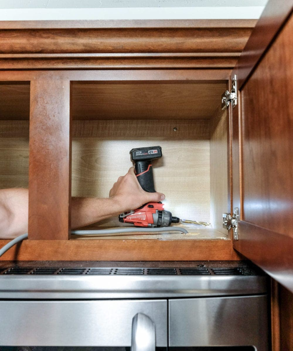 drilling a hole in a kitchen cabinet to add under cabinet lighting