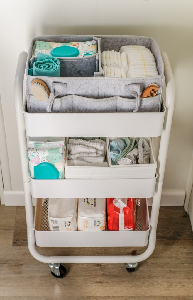 closeup of three tier utility cart with baby diapers, wipes and other supplies organized
