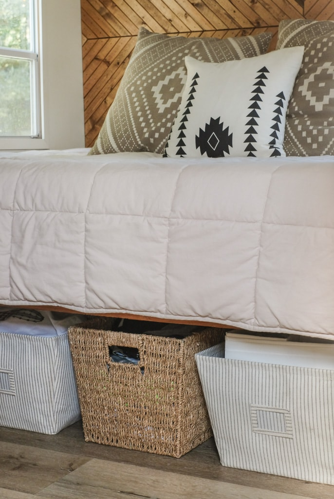 an organized bedroom with storage baskets under the bed