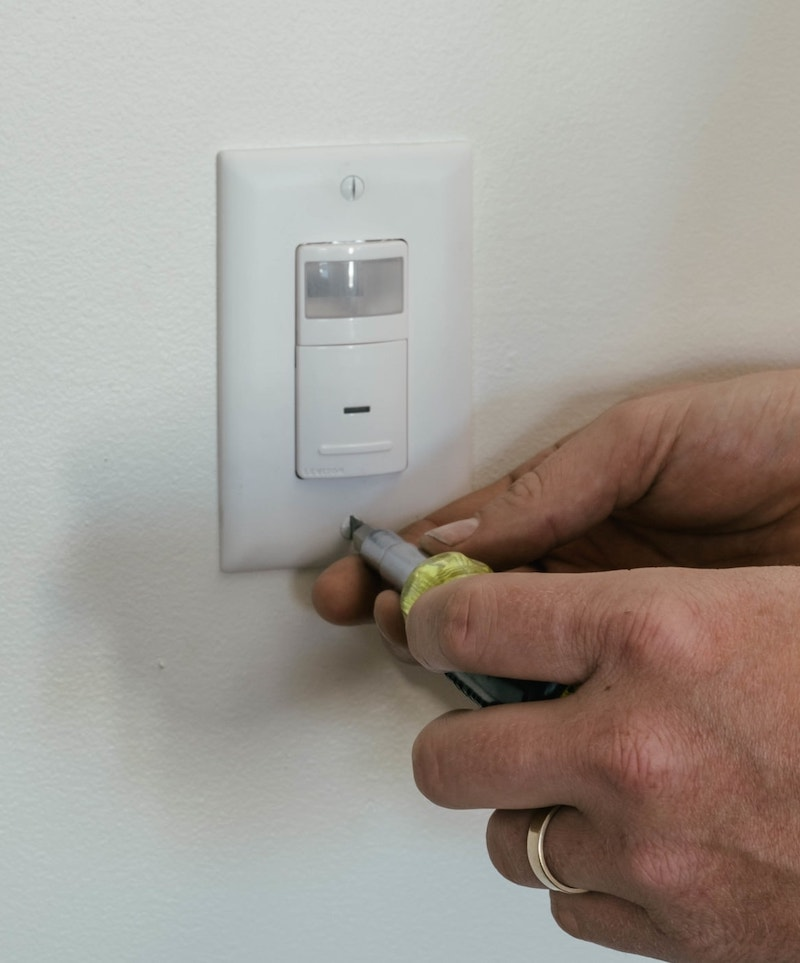 using a Klein Multi tool screwdriver to tighten a light switch cover plate