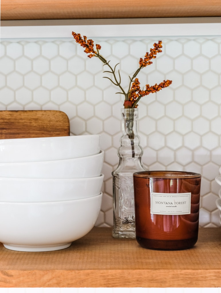 a kitchen shelf decorated for fall with a Montana forest candle
