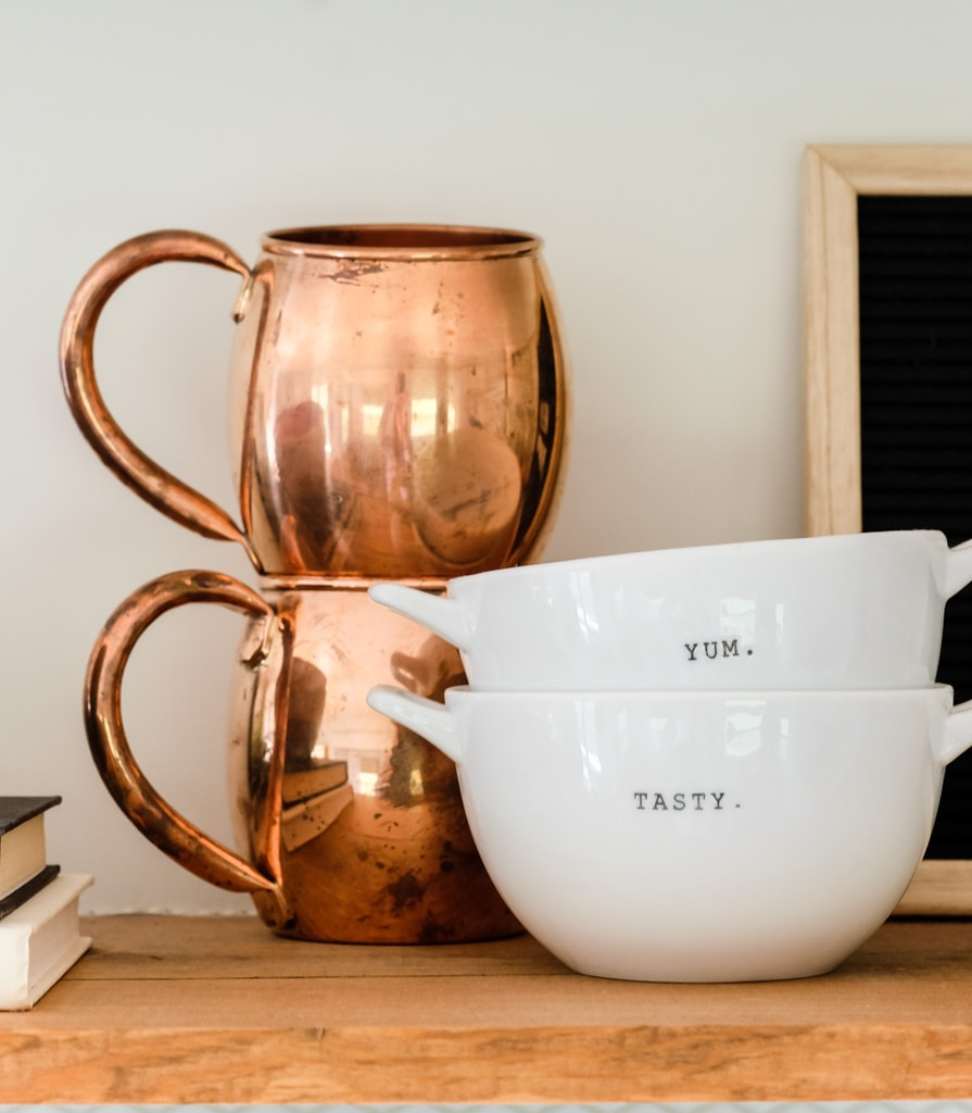 copper mugs and soup bowls on a shelf as fall decor