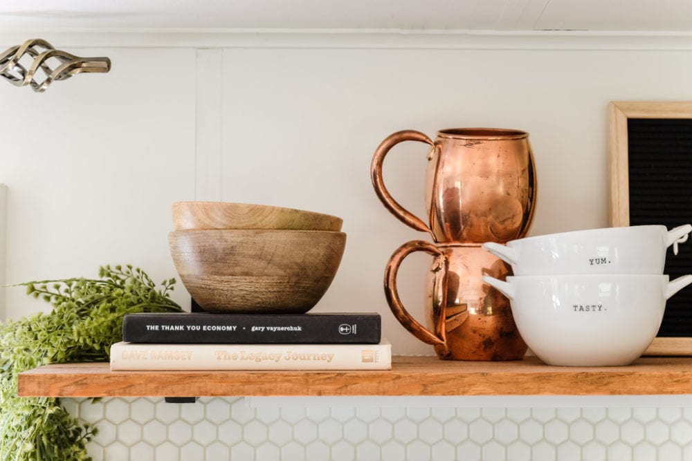 open shelving decorated with books, greenery, wood bowls and copper mugs