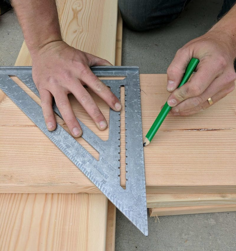 using a speed square to mark lumber with a carpenter pencil
